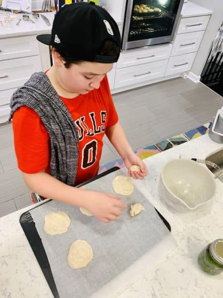 teenage boy baking communion bread in kitchen