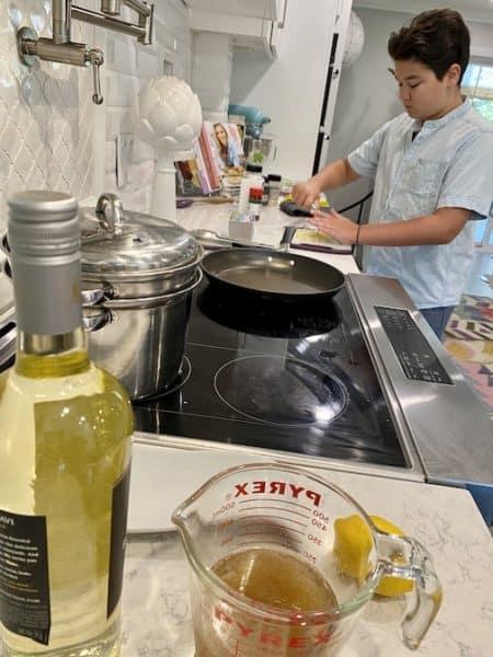 Britton Cone cooks shrimp scampi in kitchen