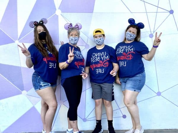 Disney family in masks in front of Magic Kingdom Purple Wall 2020